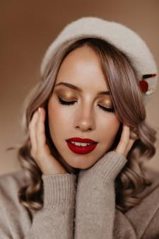 Retrato de close-up de mulher relaxada com cabelo loiro encaracolado em pé na parede marrom