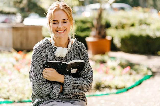 Retrato de close-up de mulher sentada em uma estufa com fones de ouvido e livro