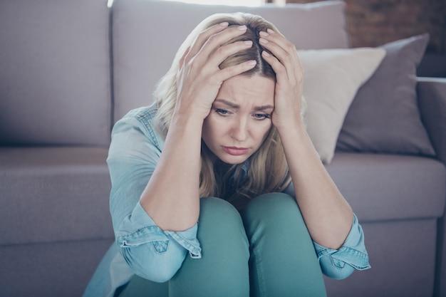 Retrato de close-up de mulher taciturna e miserável sentada no chão, tocando a cabeça