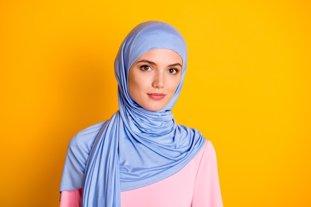 Retrato de close-up de muslimah atraente de conteúdo calmo e pacífico usando hijab isolado sobre fundo de cor amarela vibrante