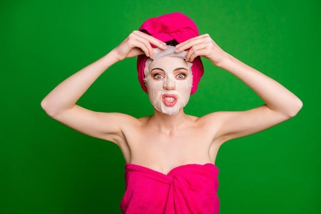 Retrato de close-up de senhora furiosa usando turbante removendo procedimento de máscara facial feia fazendo careta isolada em fundo de cor verde brilhante