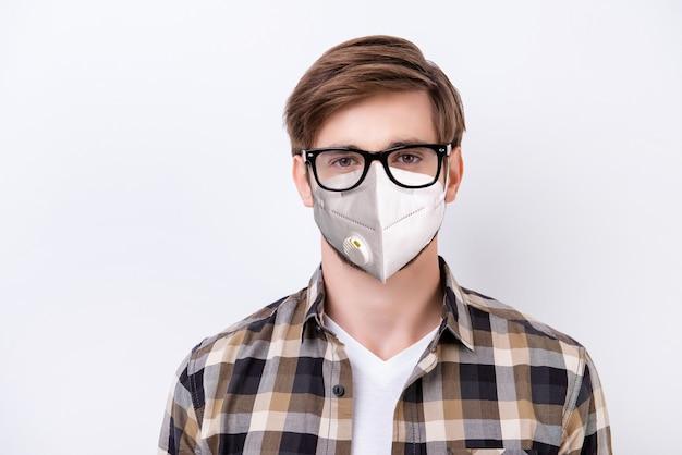 Retrato de close-up de um cara atraente e saudável usando respirador reutilizável n95 máscara parar patógeno vírus poluição atmosférica poluição do ar distância social isolada sobre fundo cinza