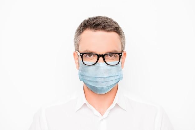 Retrato de close-up de um cara de conteúdo atraente usando máscara de gaze azul para evitar doenças, medidas preventivas, conceito de vida saudável isolado em um fundo de cor branca clara