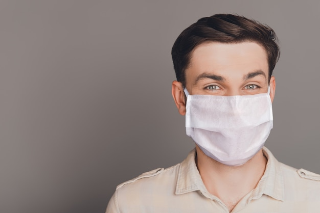 Retrato de close-up de um cara moreno atraente usando máscara branca de gaze reutilizável parar patógeno respiratório doença cov ncov mers conceito cópia espaço isolado no fundo de cor cinza