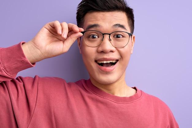Retrato de close-up de um homem chinês simpático em óculos que reage emocionalmente a algo, com a boca aberta