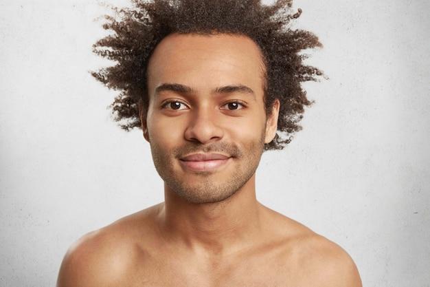 Retrato de close up de um homem condifente de pele escura com cerdas, cabelos crespos e lábios carnudos