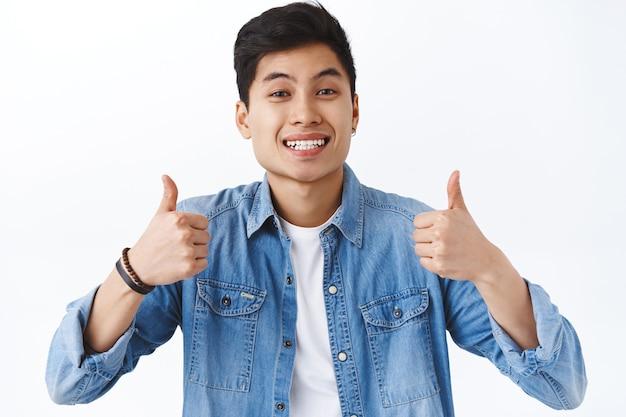 Retrato de close-up de um jovem asiático alegre recomendar produto ou serviço da empresa, mostrar o polegar para cima e sorrir, acenar concordando, aprovar e gostar da ideia, parede branca