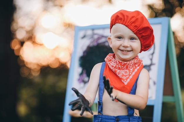 Retrato de close-up de um menino que sorri de vergonha e se alegra com a tinta nas mãos ao pôr do sol