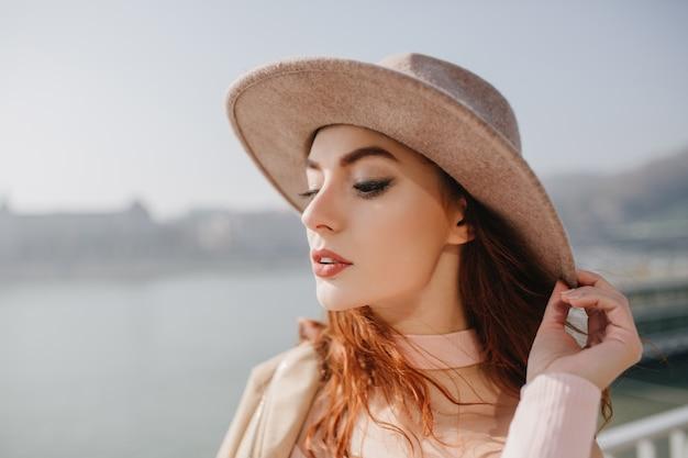 Retrato de close-up de uma adorável mulher ruiva curtindo o sol
