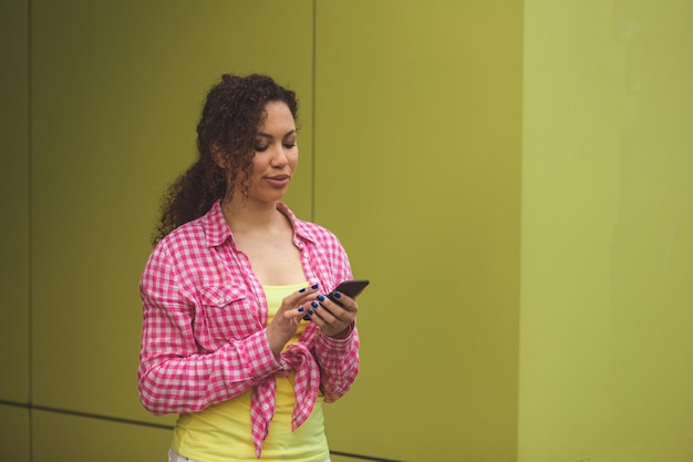 Retrato de close-up de uma atraente garota afro-americana com cabelo encaracolado e pele perfeita e saudável segurando um telefone celular e olhando para a tela com expressão concentrada enquanto assiste a vídeos online