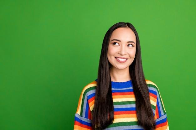 Retrato de close-up de uma atraente garota curiosa e alegre usando um pulôver listrado pensando na cópia do espaço isolado sobre um fundo de cor verde brilhante