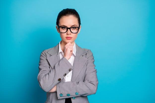 Retrato de close-up de uma atraente mulher de negócios de conteúdo inteligente, pensando, tocando o queixo isolado sobre um fundo de cor azul brilhante