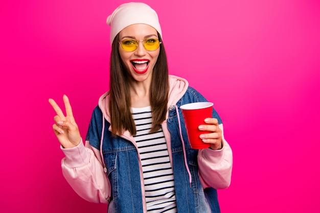 Retrato de close-up de uma bela garota atraente adorável muito alegre alegre segurando na mão uma xícara de café saboroso mostrando o sinal v isolado na cor rosa fúcsia vibrante de brilho vívido brilhante