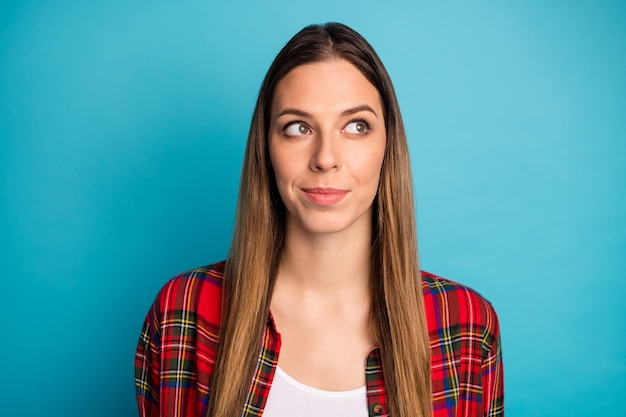 Retrato de close-up de uma bela garota de cabelos compridos inteligente, atraente, adorável, curiosa, vestindo uma camisa xadrez, criando uma solução isolada em um fundo de cor azul vibrante de brilho vívido brilhante
