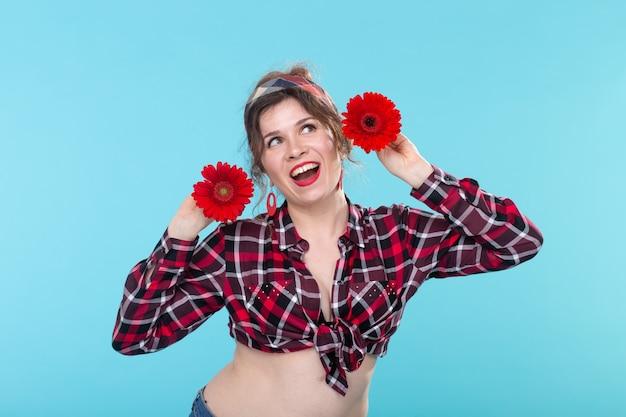 Retrato de close-up de uma bela jovem segurando flores vermelhas com diferentes corações nas mãos