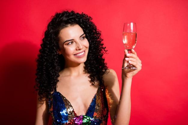 Retrato de close-up de uma encantadora garota alegre de cabelos ondulados bebendo vinho, se divertindo, isolado em um fundo de cor vermelha brilhante