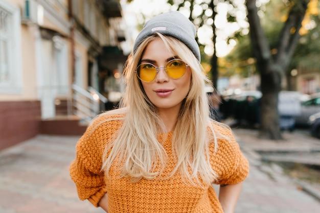 Retrato de close-up de uma fofa loira de cabelos compridos em pé no meio da rua