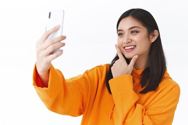 Retrato de close-up de uma garota asiática moderna elegante com capuz laranja, tirando uma selfie com o celular, posando e sorrindo como vídeo gravado, blogueira experimentando novos filtros de foto, parede branca de pé