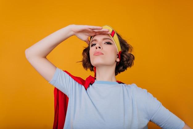 Retrato de close-up de uma garota atraente em uma camisa azul em uma pose confiante no espaço amarelo