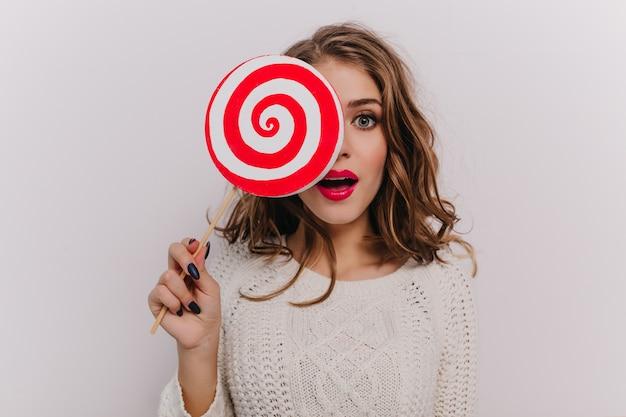 Retrato de close-up de uma garota cacheada de olhos cinza com lábios vermelhos cobrindo o rosto com um doce enorme