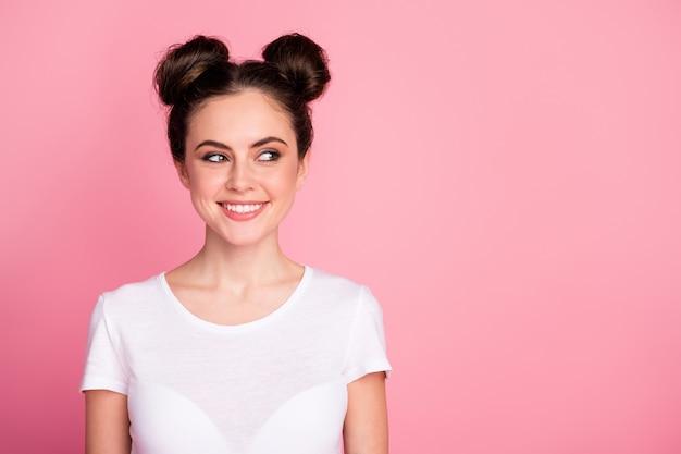 Retrato de close-up de uma garota curiosa encantadora olhando de lado, suponho isolado sobre um fundo de cor rosa