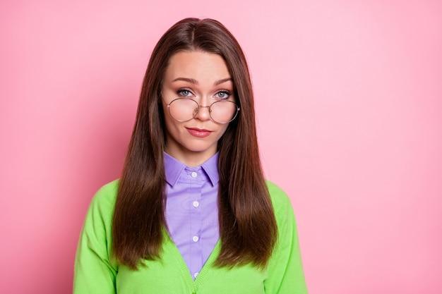 Retrato de close-up de uma garota de cabelos castanhos duvidosa, cética e experiente, olhando para você, desconfiada, isolada sobre um fundo de cor rosa pastel