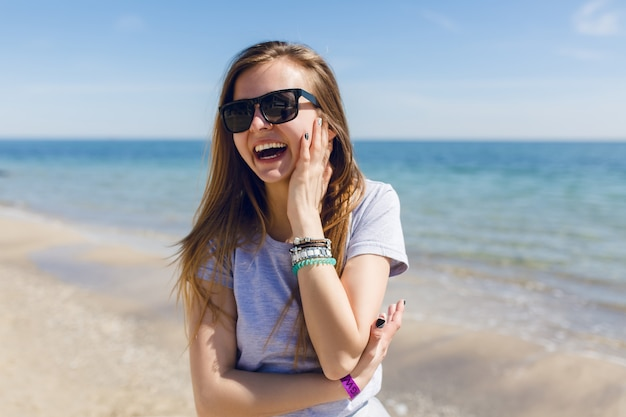 Retrato de close-up de uma jovem bonita com cabelo comprido na praia