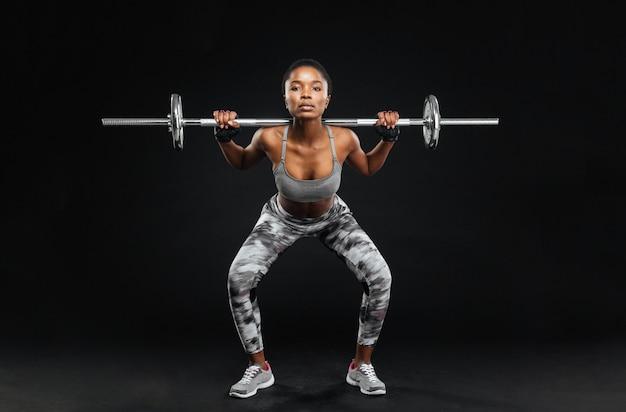Retrato de close-up de uma jovem fitness fazendo agachamento com barra na academia, isolado em uma parede preta