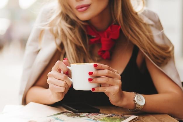 Retrato de close-up de uma jovem graciosa com pele bronzeada e unhas vermelhas segurando um copo de bebida quente
