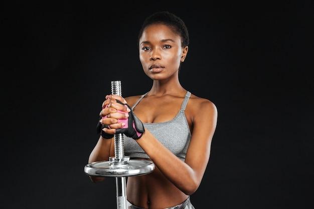 Retrato de close-up de uma jovem mulher fazendo exercícios com peso na academia, isolado em uma parede preta