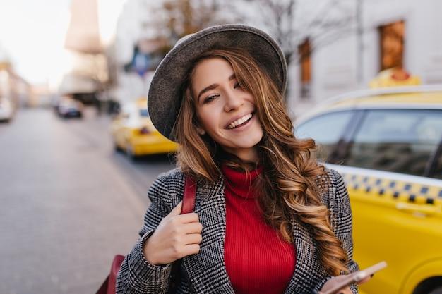 Retrato de close-up de uma jovem refinada com maquiagem nude sorrindo enquanto posava na avenida pela manhã