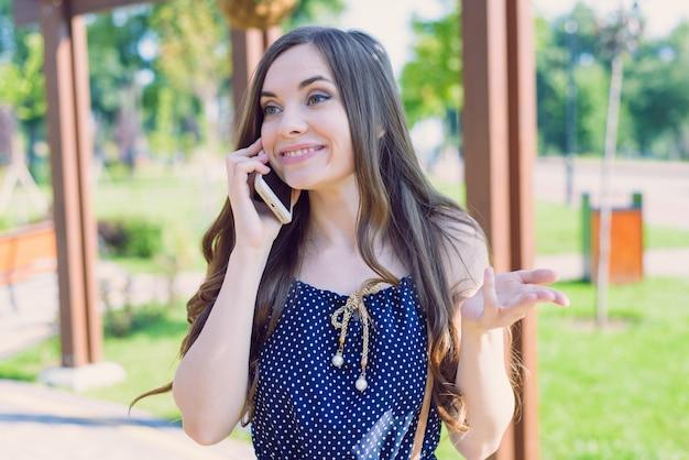 Retrato de close-up de uma linda adolescente atraente ligando para a namorada, contando notícias engraçadas e engraçadas, gesticulando com a mão
