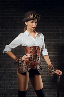 Retrato de close-up de uma linda garota steampunk em lingerie e meias, chapéu e óculos de proteção.