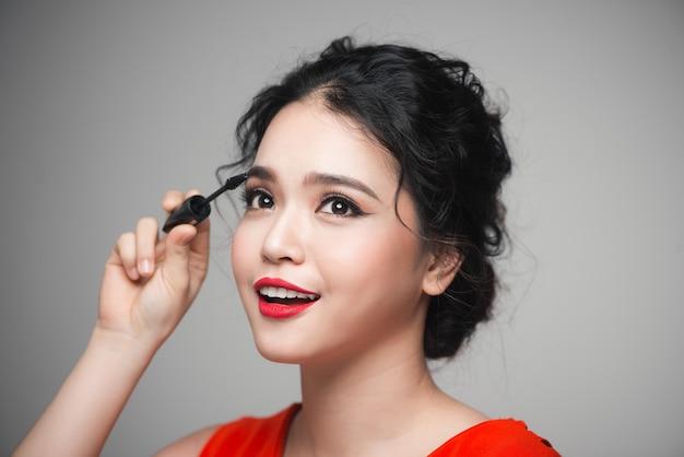 Retrato de close-up de uma linda garota tocando rímel preto nos cílios