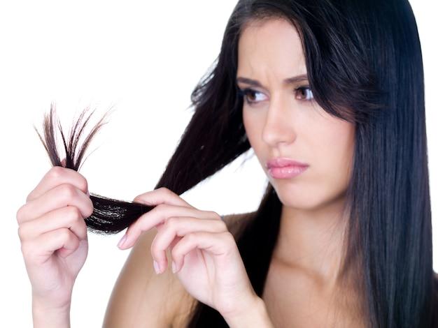 Retrato de close-up de uma linda jovem triste por causa das pontas emaranhadas de seus longos cabelos - isolado