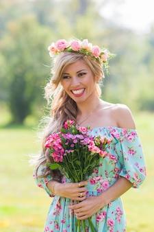 Retrato de close-up de uma linda menina loira segurando um buquê de flores no campo