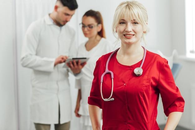 Retrato de close-up de uma médica sorridente com um uniforme vermelho e um estetoscópio