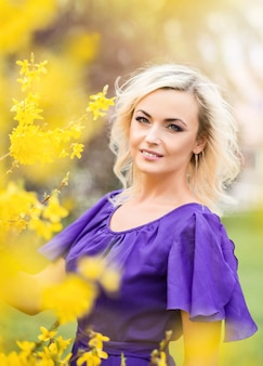 Retrato de close-up de uma menina com maquiagem profissional. mulher linda em um vestido roxo com forsítia florescendo.