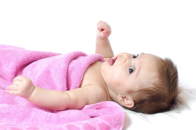 Retrato de close-up de uma menina de olhos grandes de quatro meses em uma toalha rosa sobre um branco