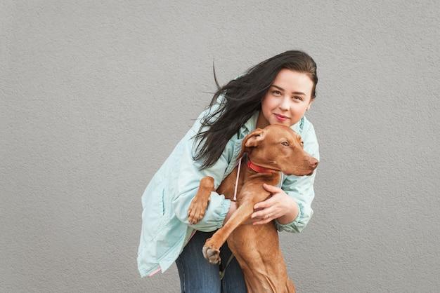 Retrato de close-up de uma mulher abraçando um cachorro
