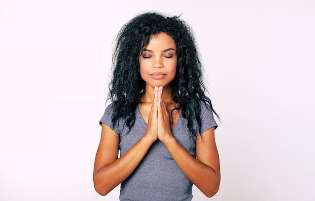 Retrato de close-up de uma mulher afro-americana serena com cabelo preto bagunçado meditando com os olhos fechados e as palmas das mãos em namaste