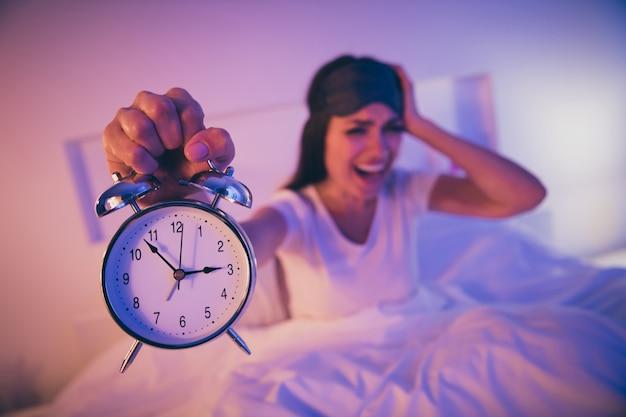 Retrato de close-up de uma mulher desesperada e preocupada segurando o relógio