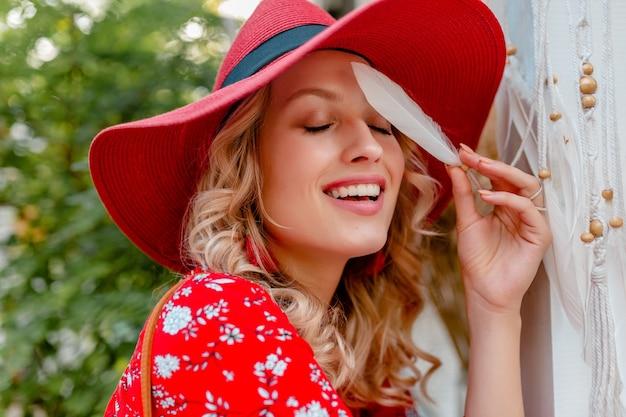 Retrato de close-up de uma mulher loira elegante e atraente sorridente com chapéu vermelho palha e blusa roupa da moda de verão segurando a pele do rosto sensual sensual de penas brancas
