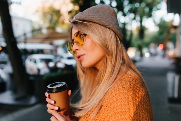 Retrato de close-up de uma mulher loira sonhadora esperando um amigo ao ar livre e bebendo café com leite