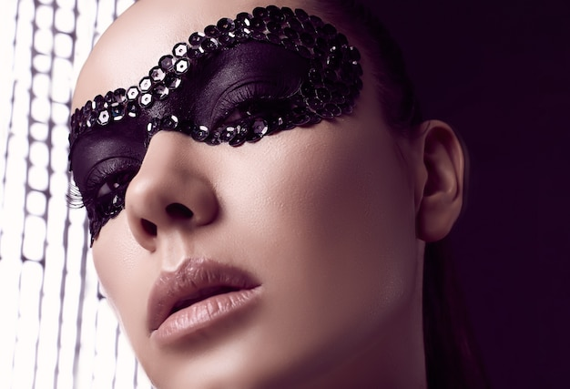 Retrato de close-up de uma mulher morena elegante e charmosa com máscara de lantejoulas posando em preto