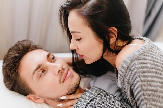 Retrato de close-up de uma senhora de cabelo preto com manicure branca, olhando com amor para o marido