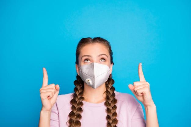 Retrato de close-up dela bonita garota atraente saudável usando máscara de segurança apontando os indicadores para cima, terapia, tratamento, doença, síndrome, isolada, sobre, brilhante, vívido, brilho, cor azul, fundo