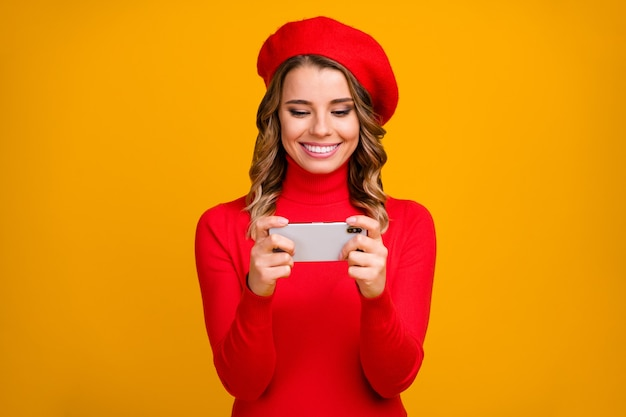 Retrato de close-up dela ela agradável atraente adorável alegre garota de cabelos ondulados segurando nas mãos celular jogando jogo estratégico de grupo de rede isolado em fundo de cor amarela vibrante brilho vívido brilhante