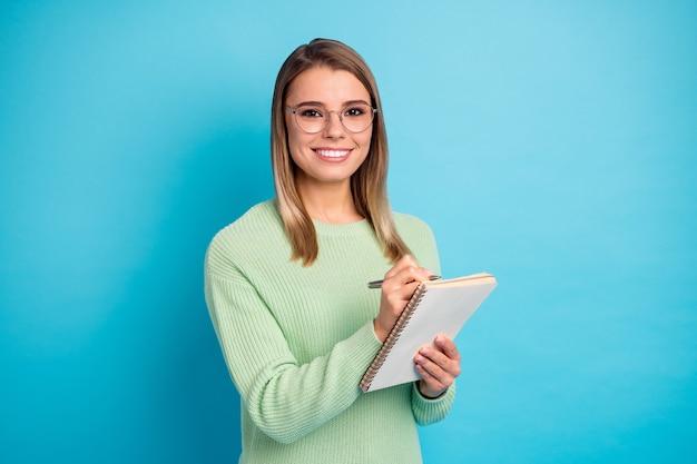 Retrato de close-up dela ela agradável atraente adorável bem-sucedido conteúdo alegre alegre menina escrevendo relatório financeiro calculando despesas isoladas sobre fundo de cor azul vibrante brilho vívido brilhante