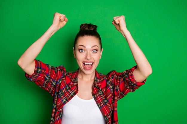Retrato de close-up dela ela agradável atraente adorável feliz viciado feliz alegre alegre garota vestindo camisa quadriculada comemorando grande vitória isolado em fundo de cor verde vibrante brilho vívido brilhante